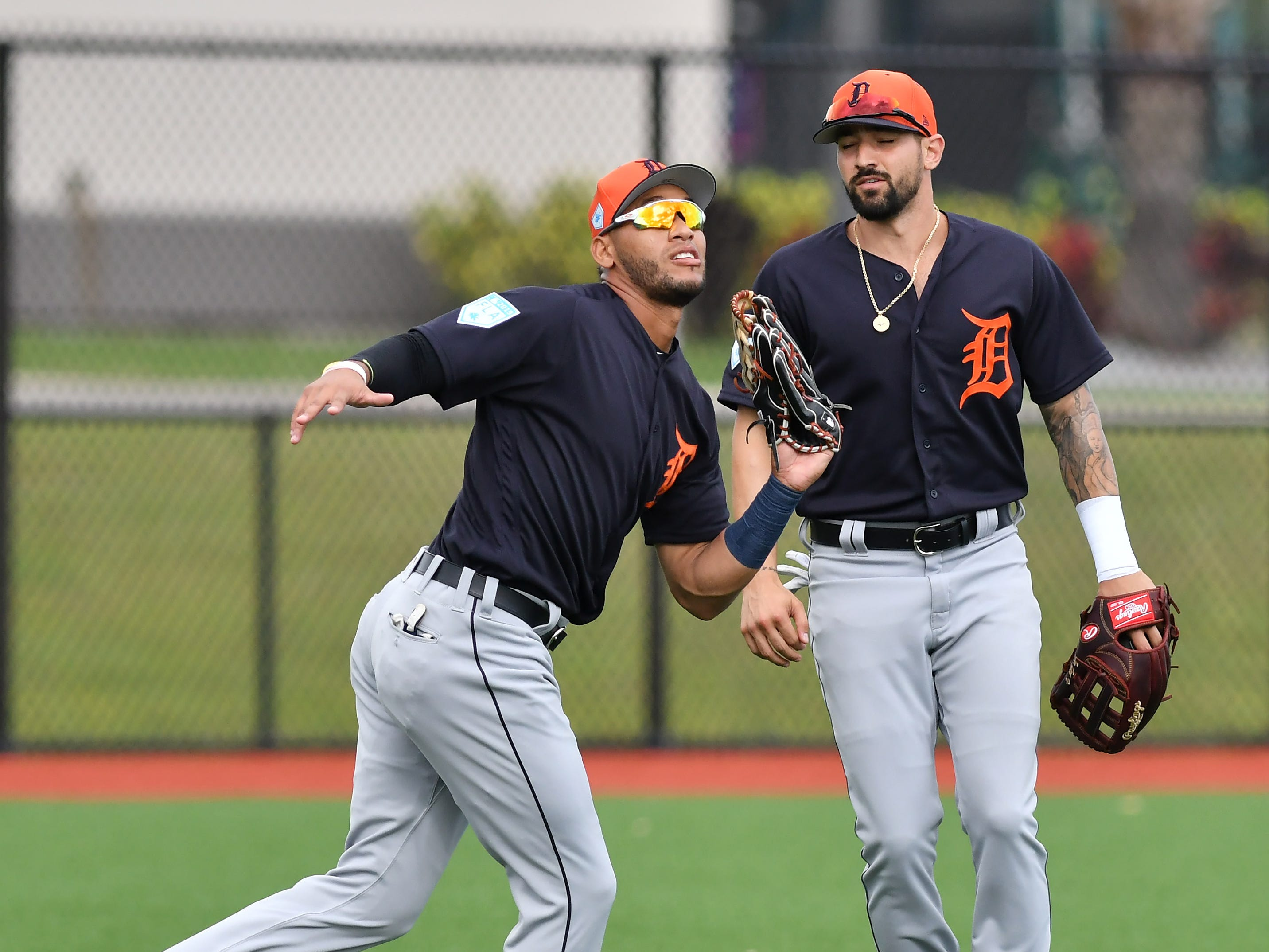Tigers outfielder Victor Reyes, left, calls off Nick Castellanos and makes the catch during outfield drills.