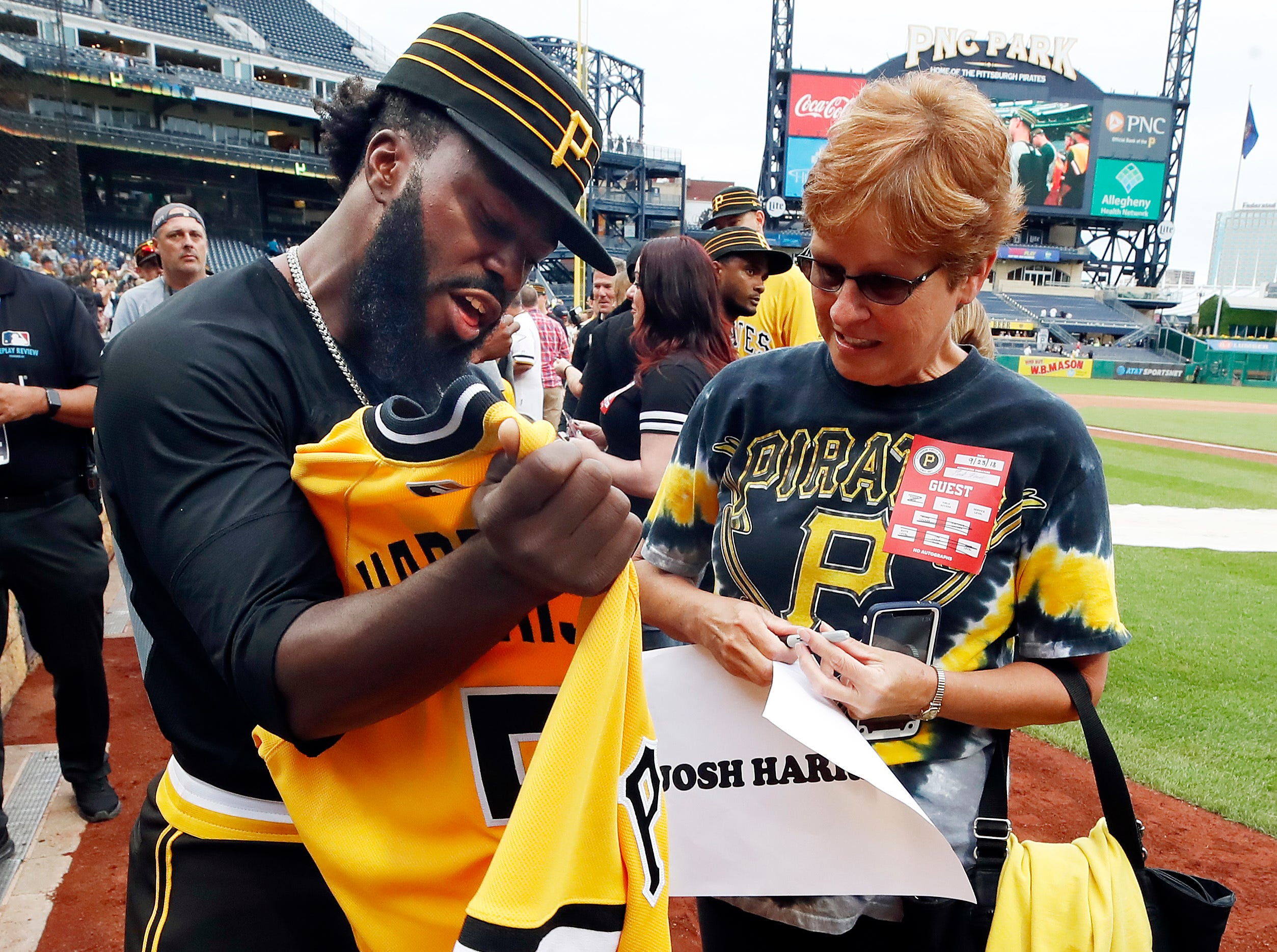 Pittsburgh Pirates' Josh Harrison gives his jersey to a fan after a loss to the Milwaukee Brewers in the last baseball game of the season at PNC Park in Pittsburgh, Sunday, Sept. 23, 2018.