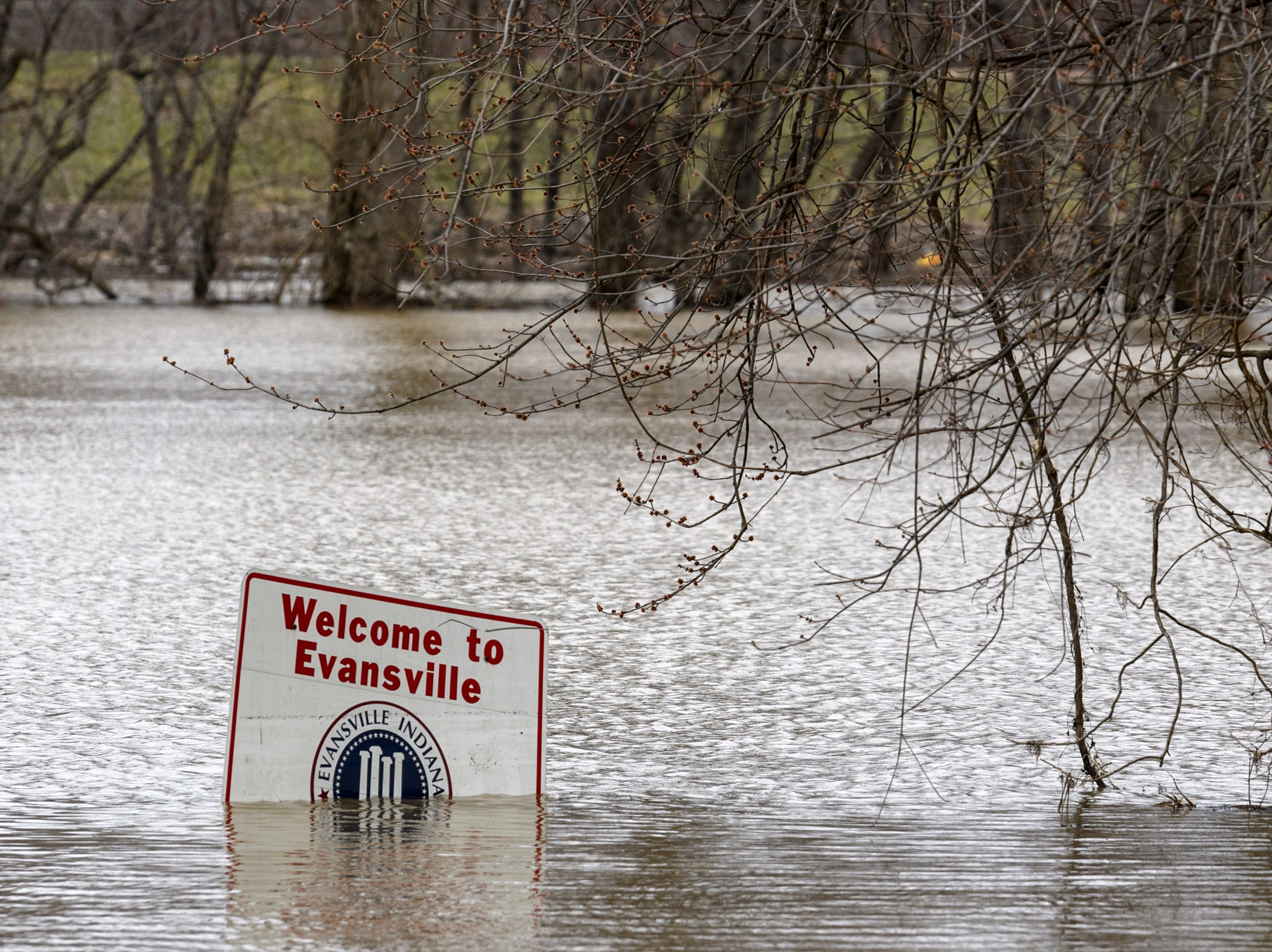 """High water reaches a """"Welcome to Evansville"""" sign seen along Waterworks Road in Evansville, Tuesday afternoon, Feb. 19, 2019."""
