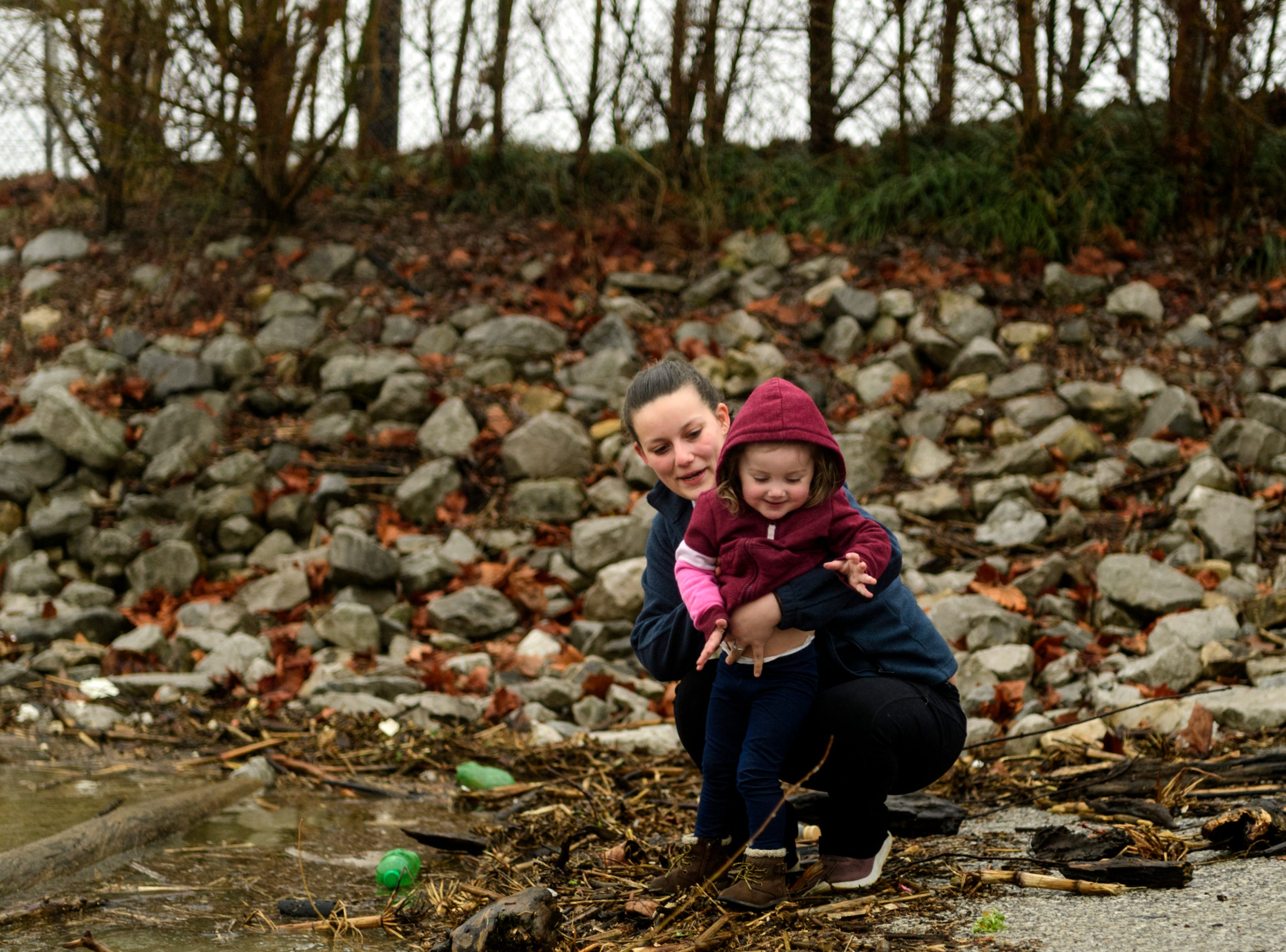 Sherri and two-year-old Hayden Rye of Mt. Vernon look for small rocks to throw into the flooded river to make a splash near Riverbend Park in downtown Mt. Vernon, Ind., Wednesday, Feb. 20, 2019. According to the National Weather Service, the flood stage was measured at 46 feet in Mount Vernon at 6 a.m. Wednesday/