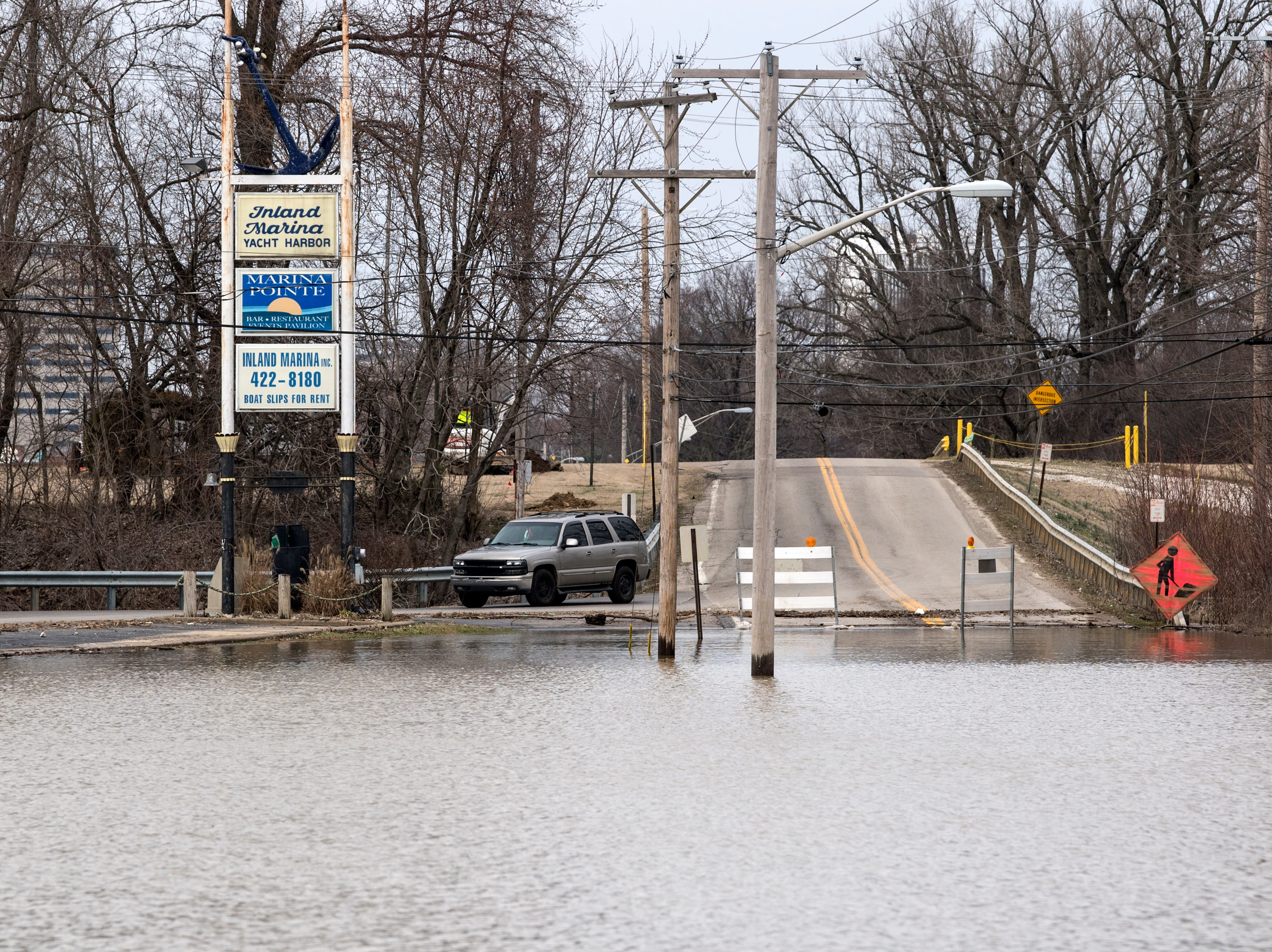 Vehicles traveling to and from Marina Point and Island Marina travel along a side road due to high water blocking a large section of Waterworks Road near the intersection of LST Drive in Evansville, Ind., Tuesday, Feb. 19, 2019.