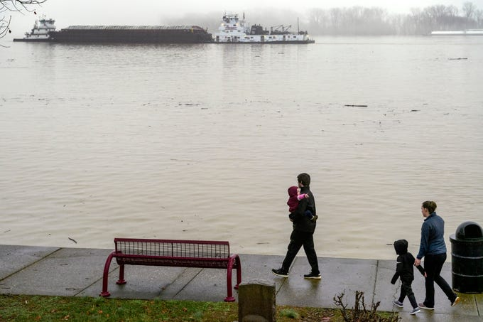 The Rye family of Mt. Vernon, Johnny carrying two-year-old Hayden as four-year-old Camden and Sherri follow behind, survey how high the water level has risen during a lunchtime walk along Riverbend Park in downtown Mt. Vernon, Ind., Wednesday, Feb. 20, 2019. According to the National Weather Service, the flood stage was measured at 46 feet in Mount Vernon at 6 a.m. Wednesday.