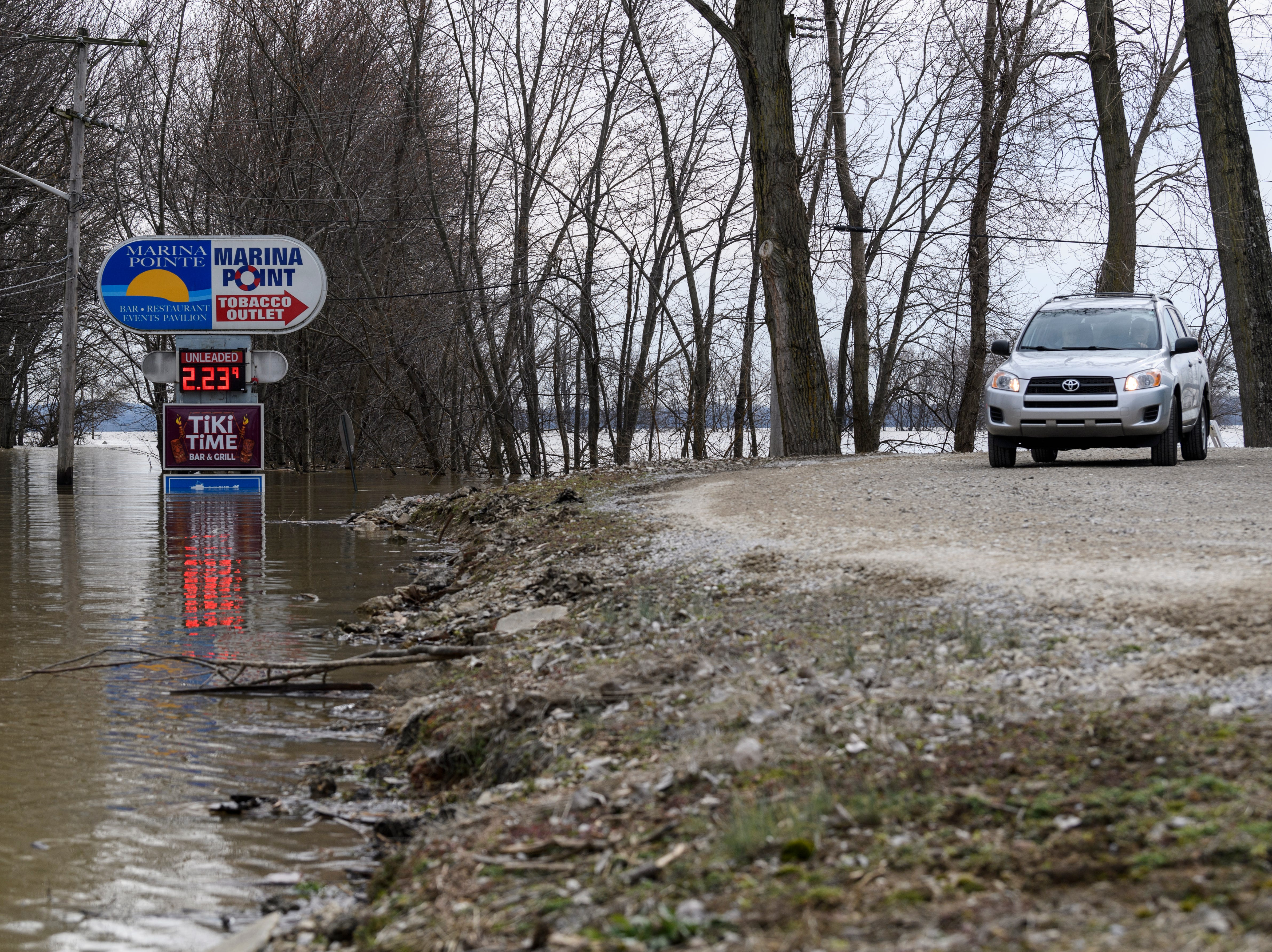 A vehicle travels from along a side road due to a flooded roadway at intersection of LST Drive and Waterworks Road in Evansville, Ind., Tuesday afternoon, Feb. 19, 2019.