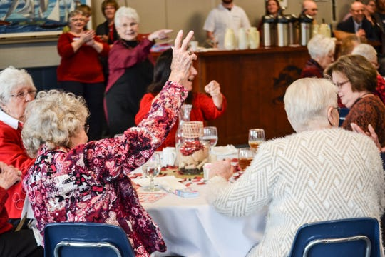 A guest raises her hand to announce her win during a game at the luncheon.