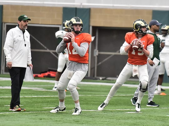 CSU coach Mike Bobo watches quarterbacks Patrick O'Brien, left, and Collin Hill throw passes during a Feb. 19, 2019, practice at the Indoor Practice Facility. (Kelly Lyell/staff)