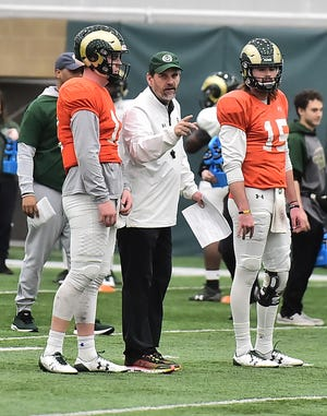 CSU football coach Mike Bobo works with quarterbacks Patrick O'Brien, left, and Collin Hill during a Feb. 19, 2019, practice at the Indoor Practice Facility. (Kelly Lyell/Staff)