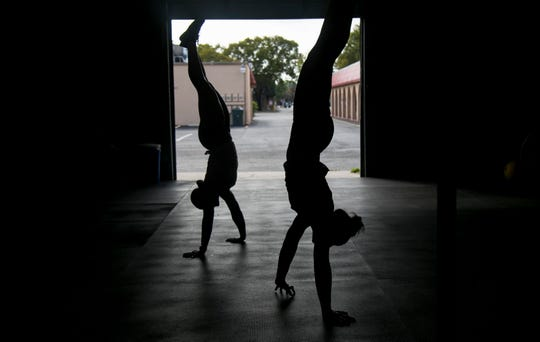 Sarina Clark, left, and Alison Cowdin do handstand walks at CrossFit 239 on Wednesday, Feb. 20, 2019. The gym is one of many across the world preparing for the 2019 CrossFit Open.