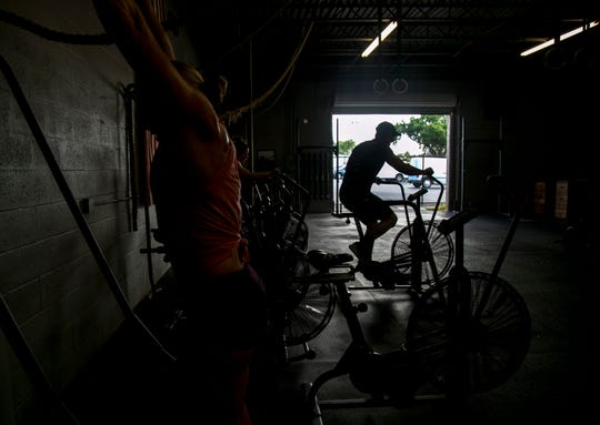 Dan Cowdin, Sarina Clark and Alison Cowdin work out Wednesday, Feb. 20, 2019, at CrossFit 239 in Fort Myers.