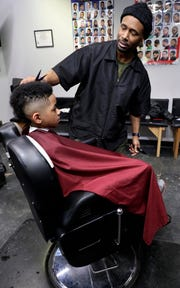 Imago Dei owner Albert Walker cuts 10-year-old Kareem Nardi's hair on Feb. 13, 2019, at his barber shop in downtown Green Bay, Wis. Sarah Kloepping/USA TODAY NETWORK-Wisconsin