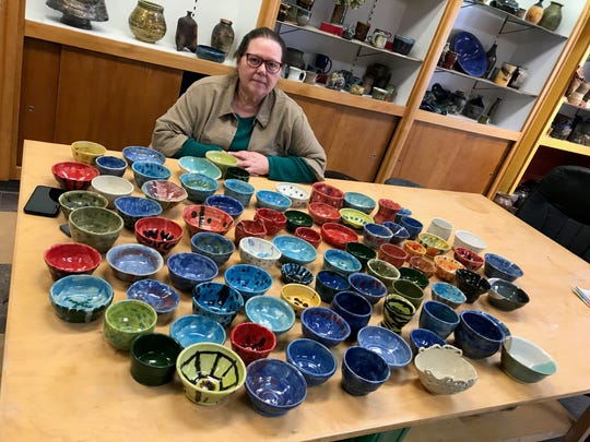 Pam Zander, president of the Zoological Society of Kewaunee County, at Clay on Steele in Algoma with some of the more than 600 clay bowls that will be for sale and used to sample locally made soups at Sunday's Zoupart benefit for the Bruemmer Park Zoo. Almost all the bowls were either made by local school students or had at least some work done by them.