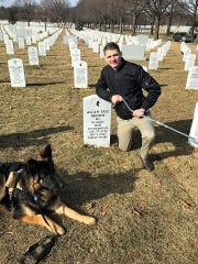 U.S. Army Specialist Winston Hencely of Georgia poses in this undated photo at the grave site of Sgt. 1st Class Allan Eric Brown, who died of injuries suffered in a suicide bombing Nov. 12, 2016. Hencely was badly injured trying to stop the bomber at Bagram Air Force Base in Afghanistan and filed a lawsuit Wednesday, Feb. 20, 2019, against the military contractor the bomber worked for.