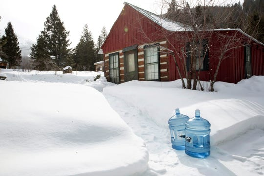 Bottles of drinking water sit outside a home in Rimini, Mont., on Feb. 18, 2019. The community was added to the Environmental Protection Agency's Superfund list in 1999. Contaminated soil in residents' yards was replaced, and the EPA has provided bottled water for a decade. But polluted water still pours from the mines and into Upper Tenmile Creek. (AP Photo/Janie Osborne)