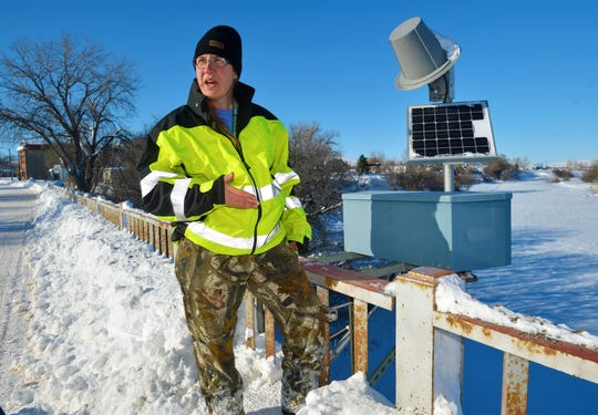 Kim Schierenbeck, a hydrologic technician with the U.S. Geologic Service, makes repairs to a river gauge at a bridge on the Missouri River in Cascade Tuesday. Ice jams along several miles of the Missouri River have caused minor flooding south of Cascade.