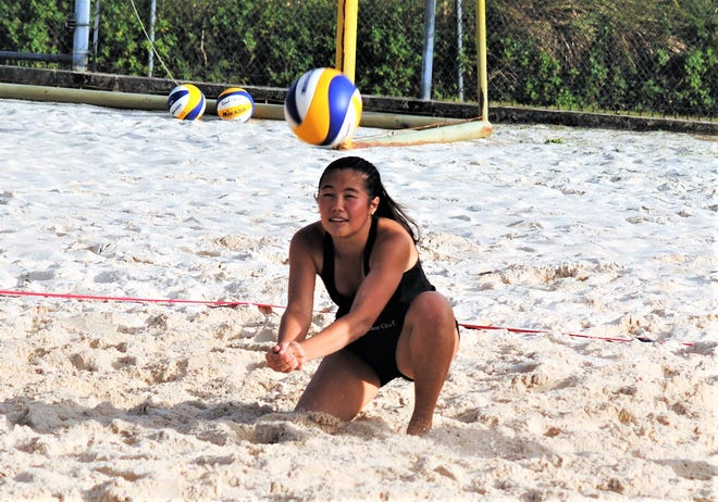 Hallie Wigsten of St. John's White goes low to pass the ball to her partner Tylee Shepherd on Feb. 19 at the Guam Football Association's sand courts. The team beat Natalie Bruch and Trinity Terlaje in two sets.