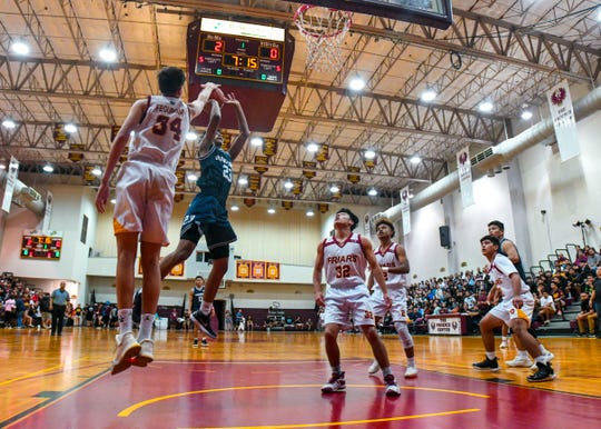 FD's Matt Fegurgur (34) denies a shot attempt by Saint Paul's Reo Aiken (23) during an IIAAG Boys Basketball game in this Feb. 20 file photo. The Friars and Warriors will compete for the league title March 15 at the University of Guam's Calvo Field House.