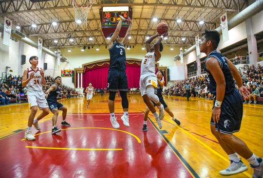 Father Duenas' Tony Quinene (2) goes up against the Warriors' Nichika Fermin (2) under the rim during their IIAAG High School Boys Basketball game at the FDMS Phoenix Center in Mangilao Feb. 20.
