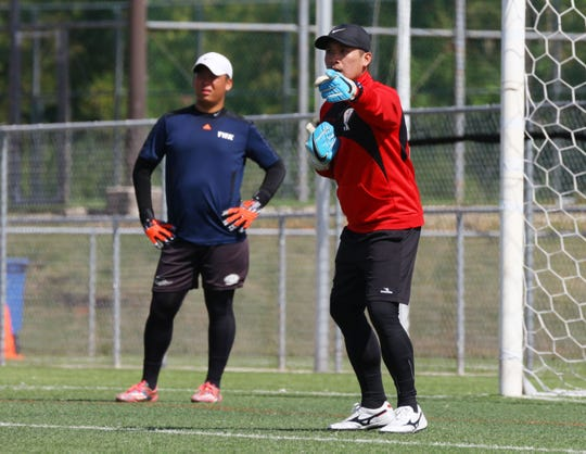 Guam Football Association goalkeeper coach instructor and AFC-licensed goalkeeper coach Ross Awa, in red, explains a training session activity with Kaito Atsuta during the course held at the GFA National Training Center Feb. 15-17.
