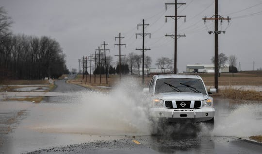 A truck drives through high water on Airline Road in Henderson County after heavy rains Tuesday night, Wednesday, February 20, 2019.