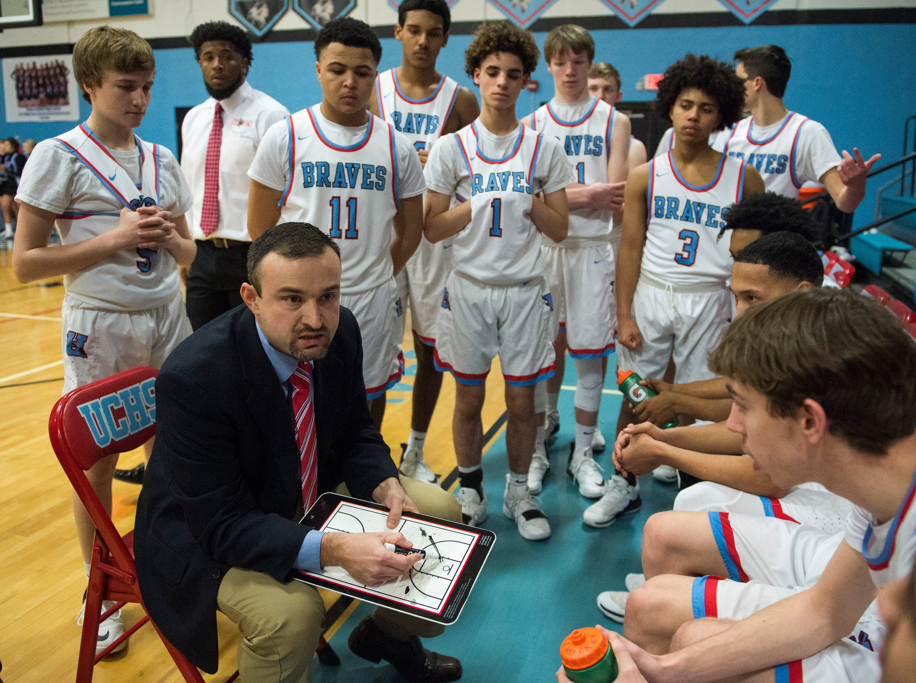 Union County's Head Coach Shane Smith gathers his team on the bench before they take on the Webster County Trojans at the Dr. Doug Hines Gymnasium in Morganfield, Ky. Tuesday, Feb. 19, 2019.