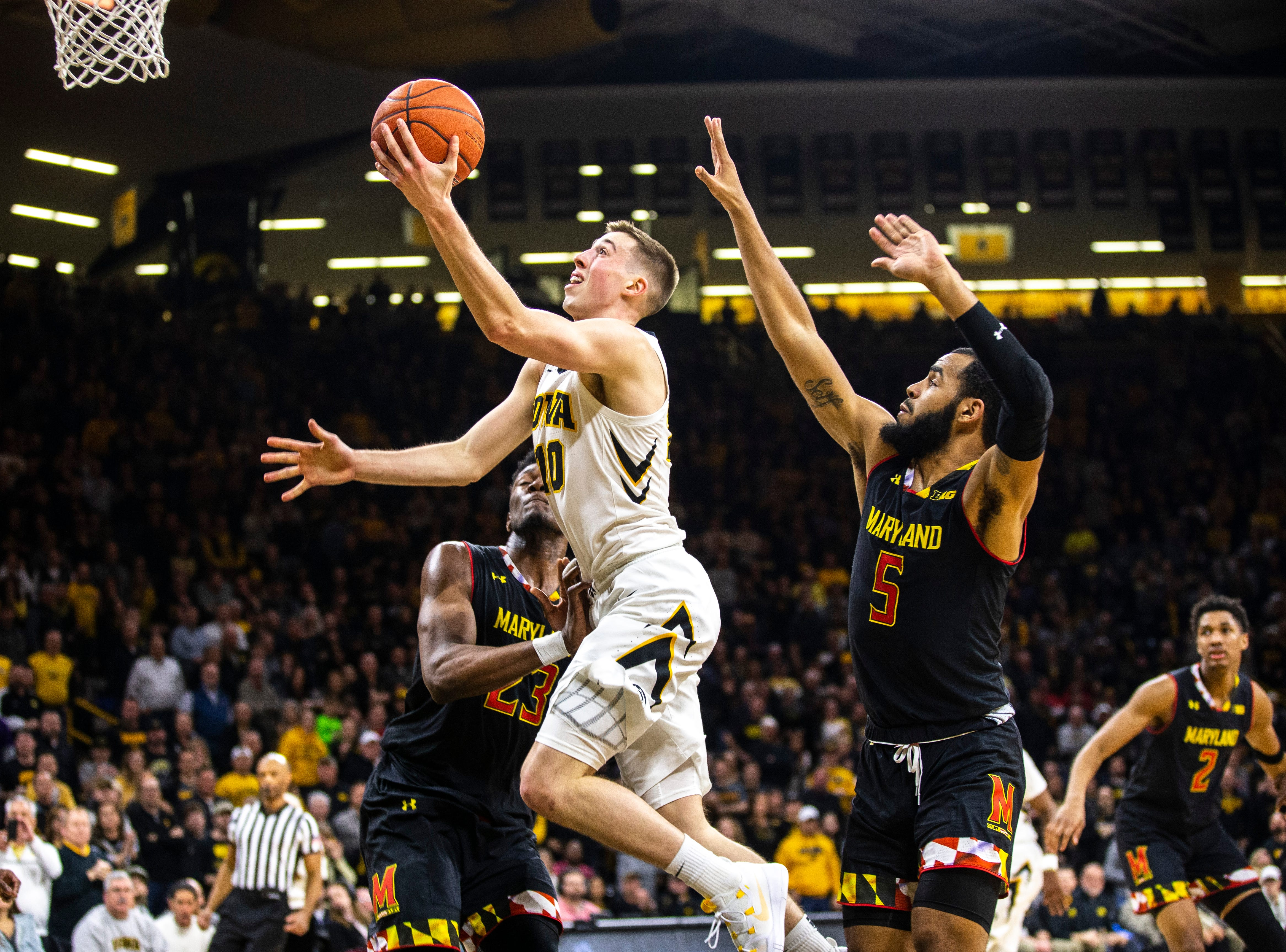 Iowa guard Joe Wieskamp (10) drives to the basket while Maryland forward Bruno Fernando (23) and Maryland guard Eric Ayala (5) defend during a NCAA Big Ten Conference men's basketball game on Tuesday, Feb. 19, 2019 at Carver-Hawkeye Arena in Iowa City, Iowa.