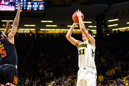 Iowa forward Nicholas Baer (51) shoots a 3-point basket while Maryland guard Eric Ayala (5) defends during a NCAA Big Ten Conference men's basketball game on Tuesday, Feb. 19, 2019 at Carver-Hawkeye Arena in Iowa City, Iowa.