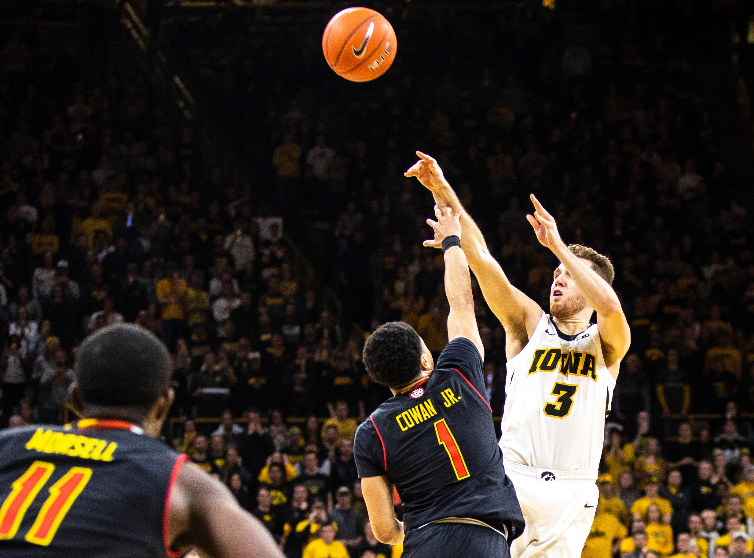 Iowa guard Jordan Bohannon (3) shoots a basket as time ticks down while Maryland guard Anthony Cowan Jr. (1) defends during a NCAA Big Ten Conference men's basketball game on Tuesday, Feb. 19, 2019 at Carver-Hawkeye Arena in Iowa City, Iowa.