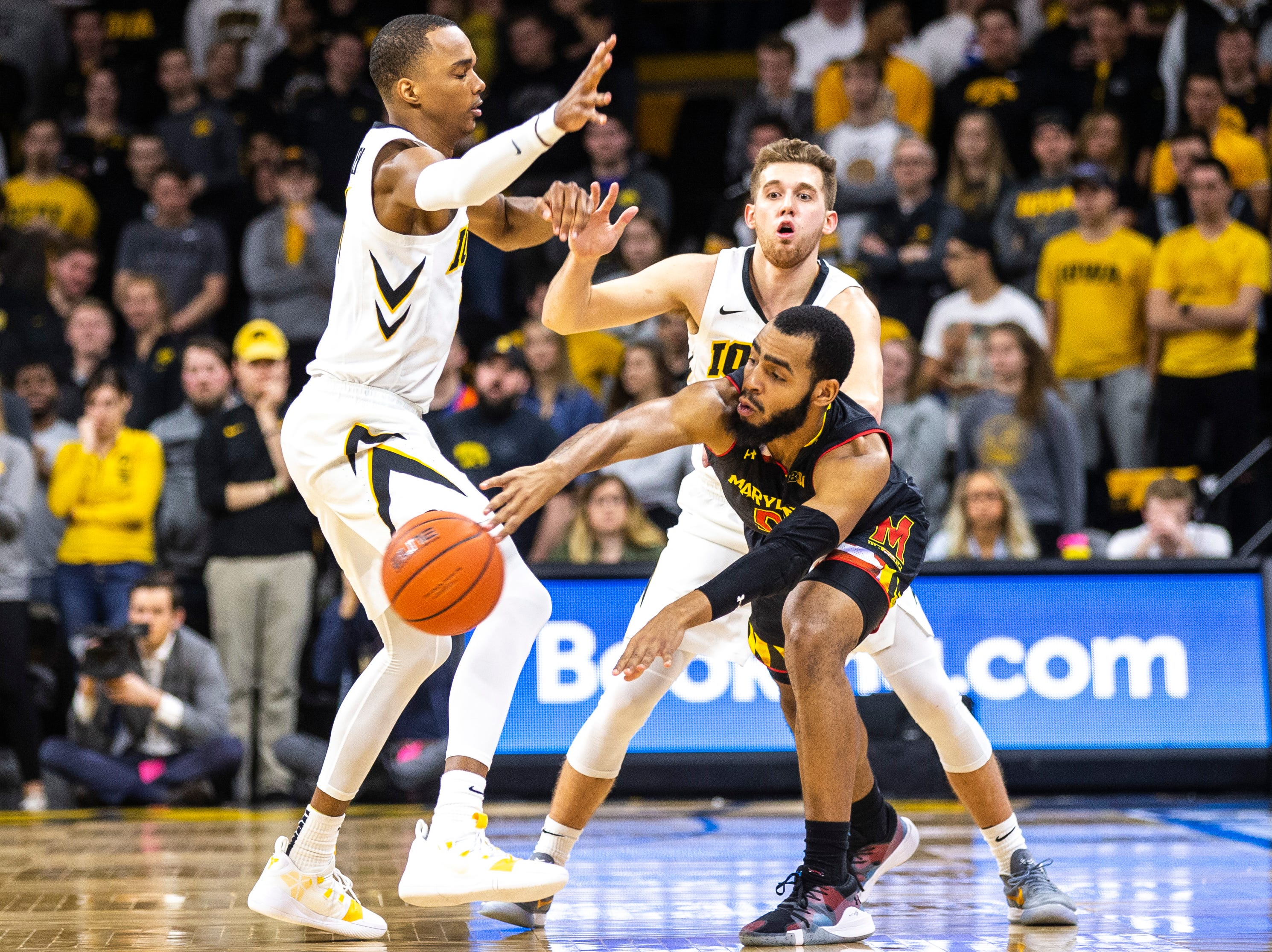 Iowa guard Jordan Bohannon (back) and Iowa guard Maishe Dailey (left) defend Maryland guard Eric Ayala (5) during a NCAA Big Ten Conference men's basketball game on Tuesday, Feb. 19, 2019 at Carver-Hawkeye Arena in Iowa City, Iowa.