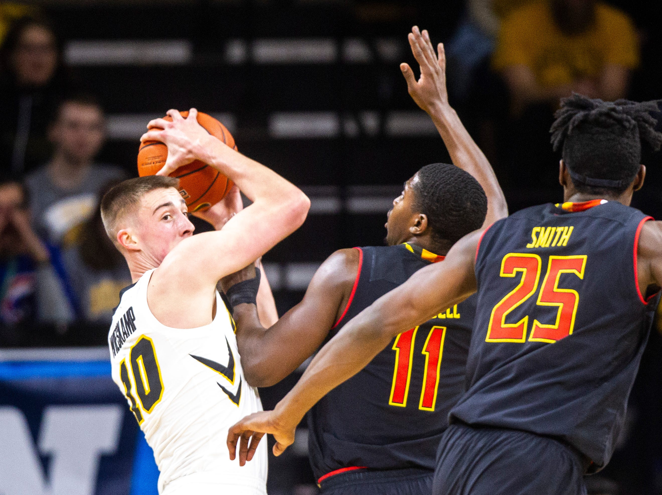 Iowa guard Joe Wieskamp (10) looks to get a pass out while Maryland guard Darryl Morsell (11) and Maryland forward Jalen Smith (25) defend during a NCAA Big Ten Conference men's basketball game on Tuesday, Feb. 19, 2019 at Carver-Hawkeye Arena in Iowa City, Iowa.