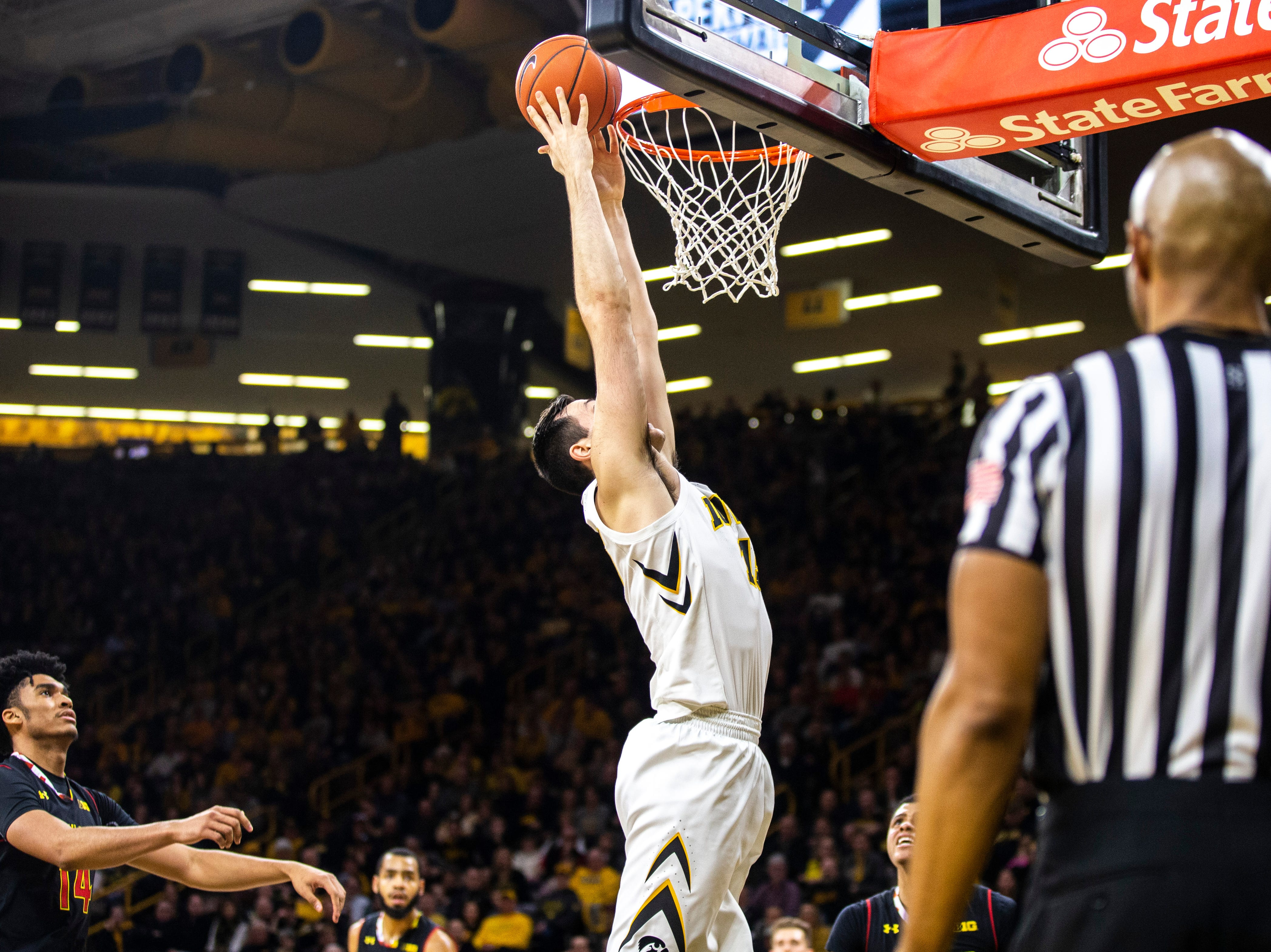 Iowa forward Ryan Kriener (15) misses a dunk while Maryland forward Ricky Lindo Jr. (14) defends during a NCAA Big Ten Conference men's basketball game on Tuesday, Feb. 19, 2019 at Carver-Hawkeye Arena in Iowa City, Iowa.