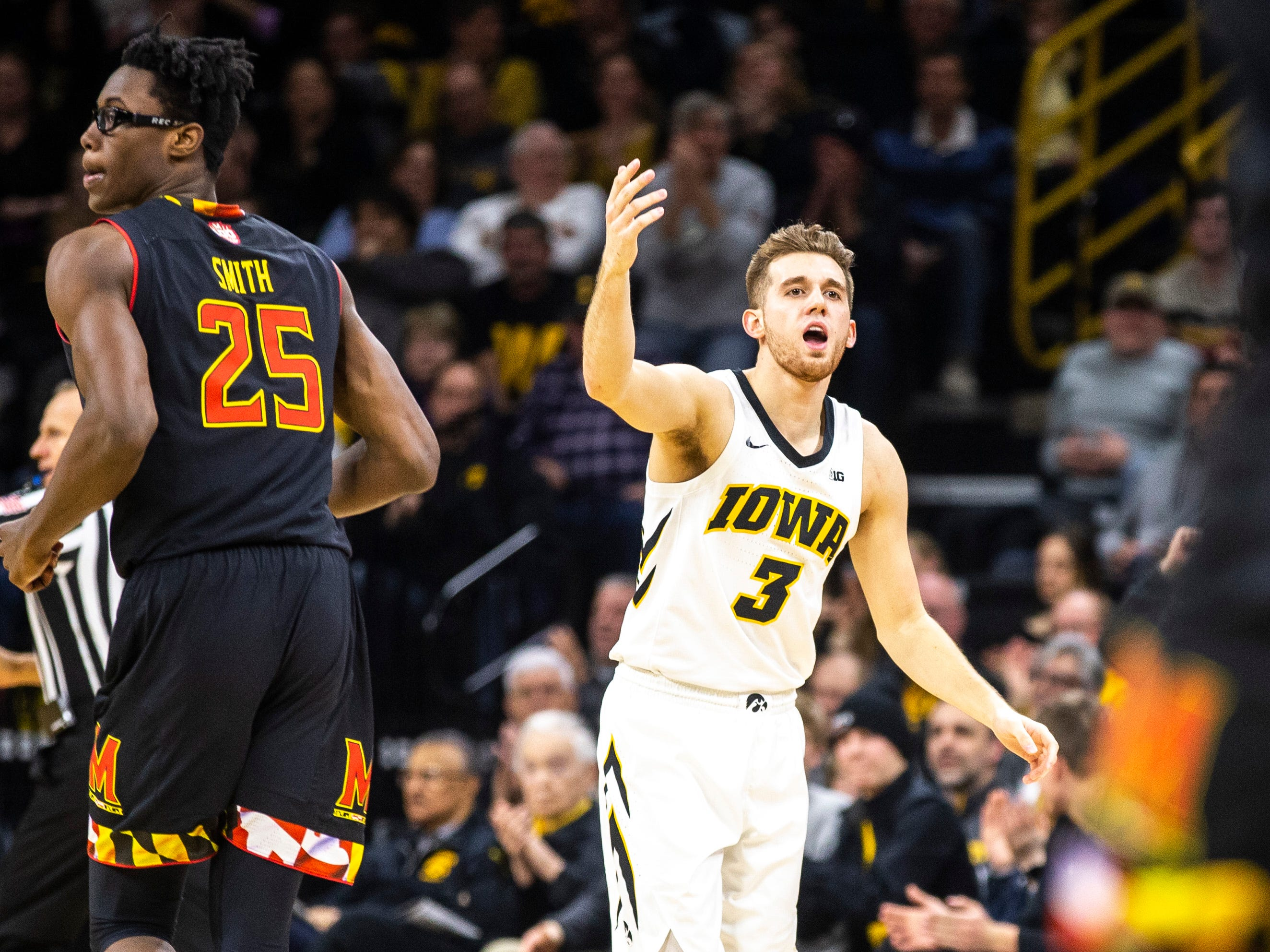 Iowa guard Jordan Bohannon (3) jumps up the crowd after making a 3-point basket while Maryland forward Jalen Smith (25) runs up court during a NCAA Big Ten Conference men's basketball game on Tuesday, Feb. 19, 2019 at Carver-Hawkeye Arena in Iowa City, Iowa.