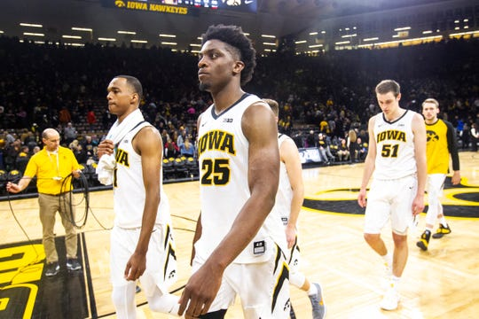 Iowa players Maishe Dailey (1), Tyler Cook (25) and Nicholas Baer (51) walk off the court after Tuesday's 66-65 home loss to Maryland.