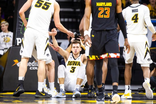 Jordan Bohannon is helped off the floor during Iowa's Feb. 19 game against Maryland. Bohannon told the Register he endured more hits to his injured right hip as the season progressed.