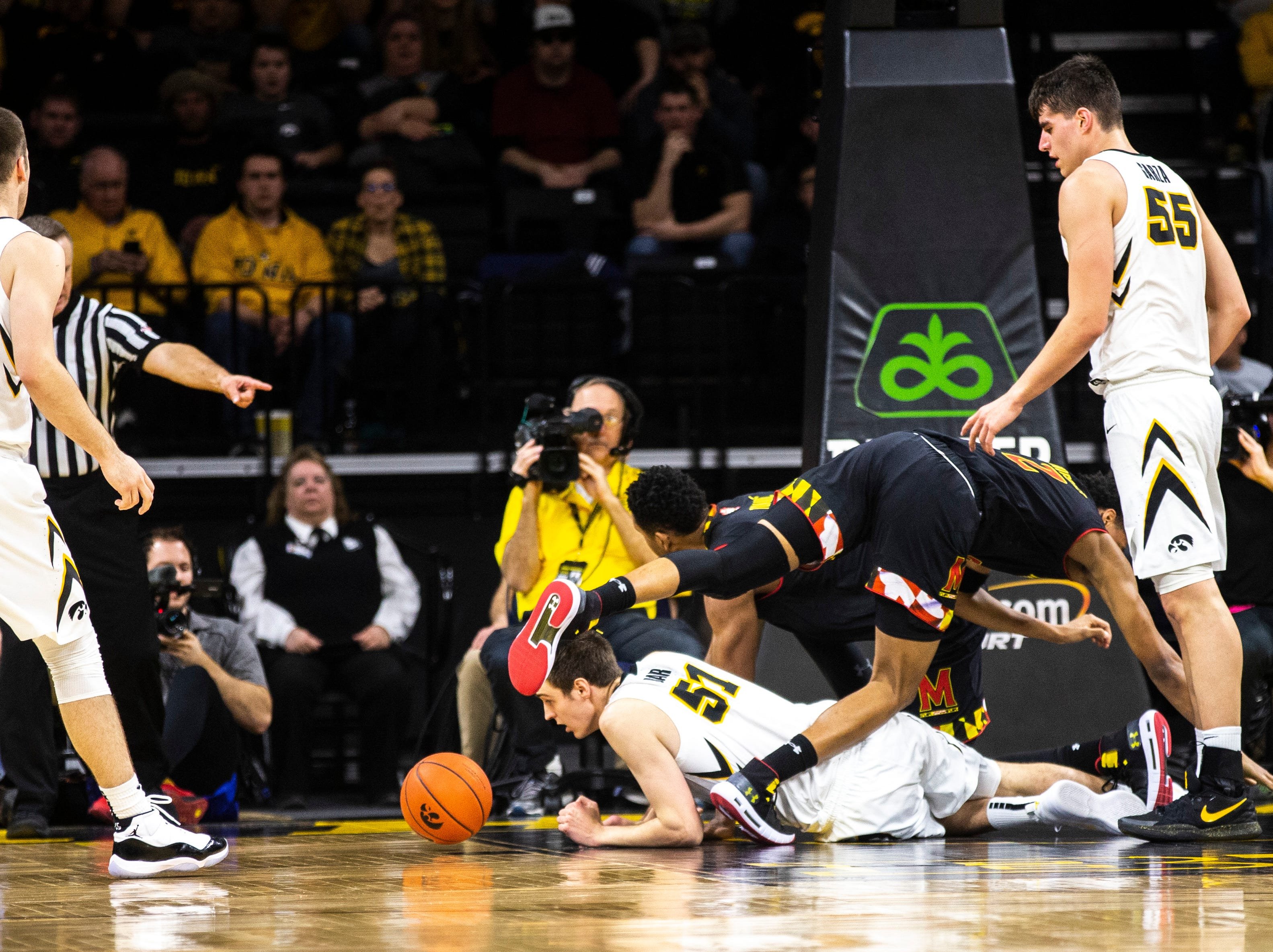 Iowa forward Nicholas Baer (51) falls to the ground while going for a rebound against Maryland guard Aaron Wiggins (2) during a NCAA Big Ten Conference men's basketball game on Tuesday, Feb. 19, 2019 at Carver-Hawkeye Arena in Iowa City, Iowa.