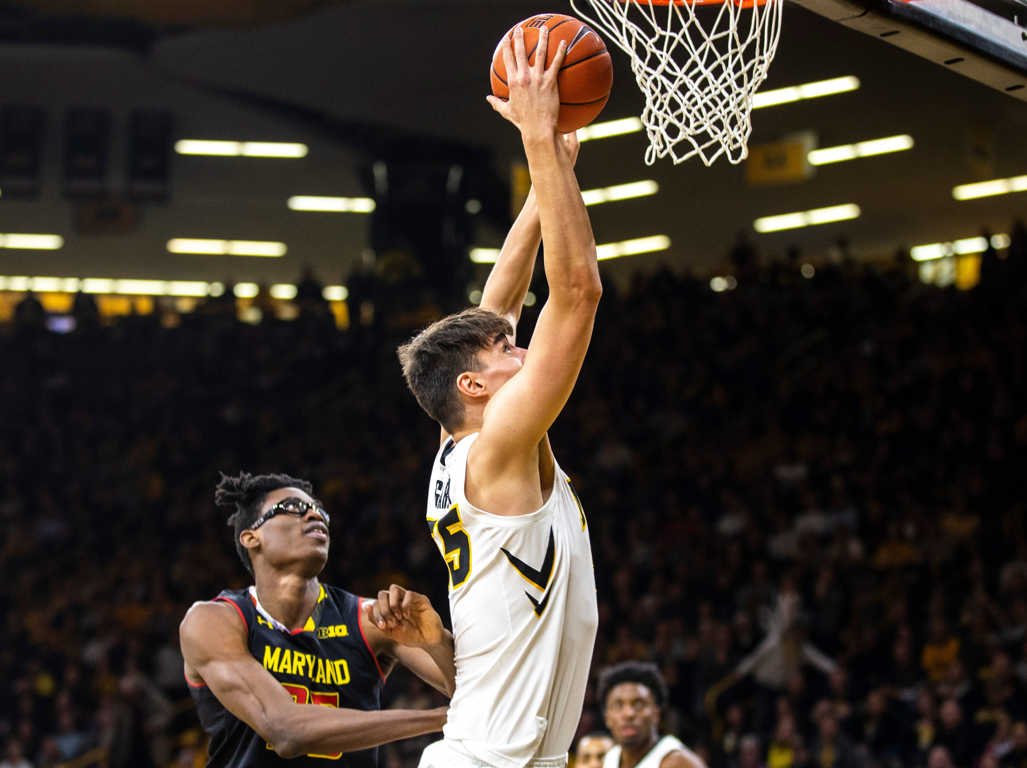 Iowa center Luka Garza (55) grabs a ball for a put-back while Maryland forward Jalen Smith, left, defends during a NCAA Big Ten Conference men's basketball game on Tuesday, Feb. 19, 2019 at Carver-Hawkeye Arena in Iowa City, Iowa.