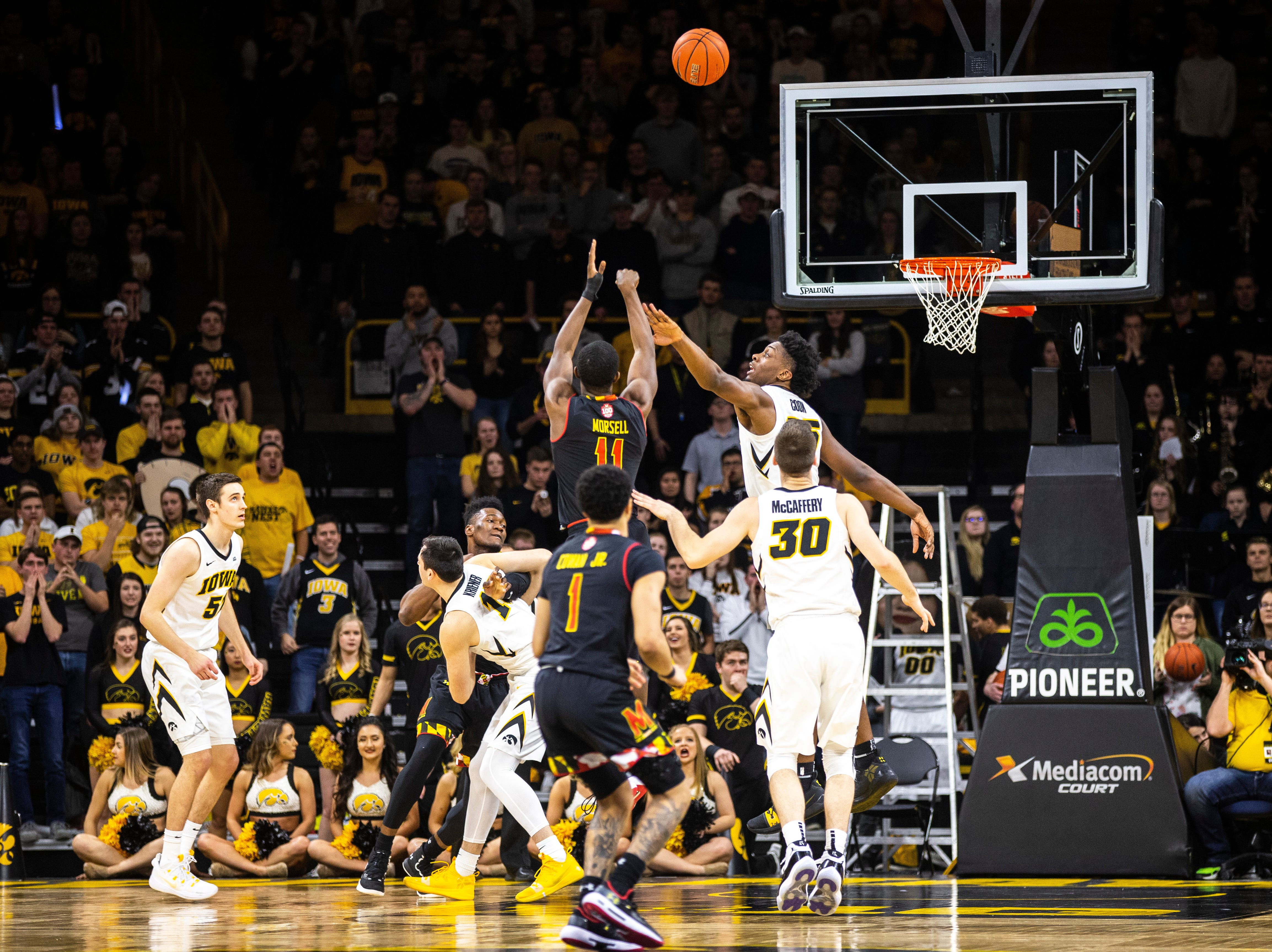 Maryland guard Darryl Morsell (11) shoots a basket while Iowa forward Tyler Cook (25) defend during a NCAA Big Ten Conference men's basketball game on Tuesday, Feb. 19, 2019 at Carver-Hawkeye Arena in Iowa City, Iowa.