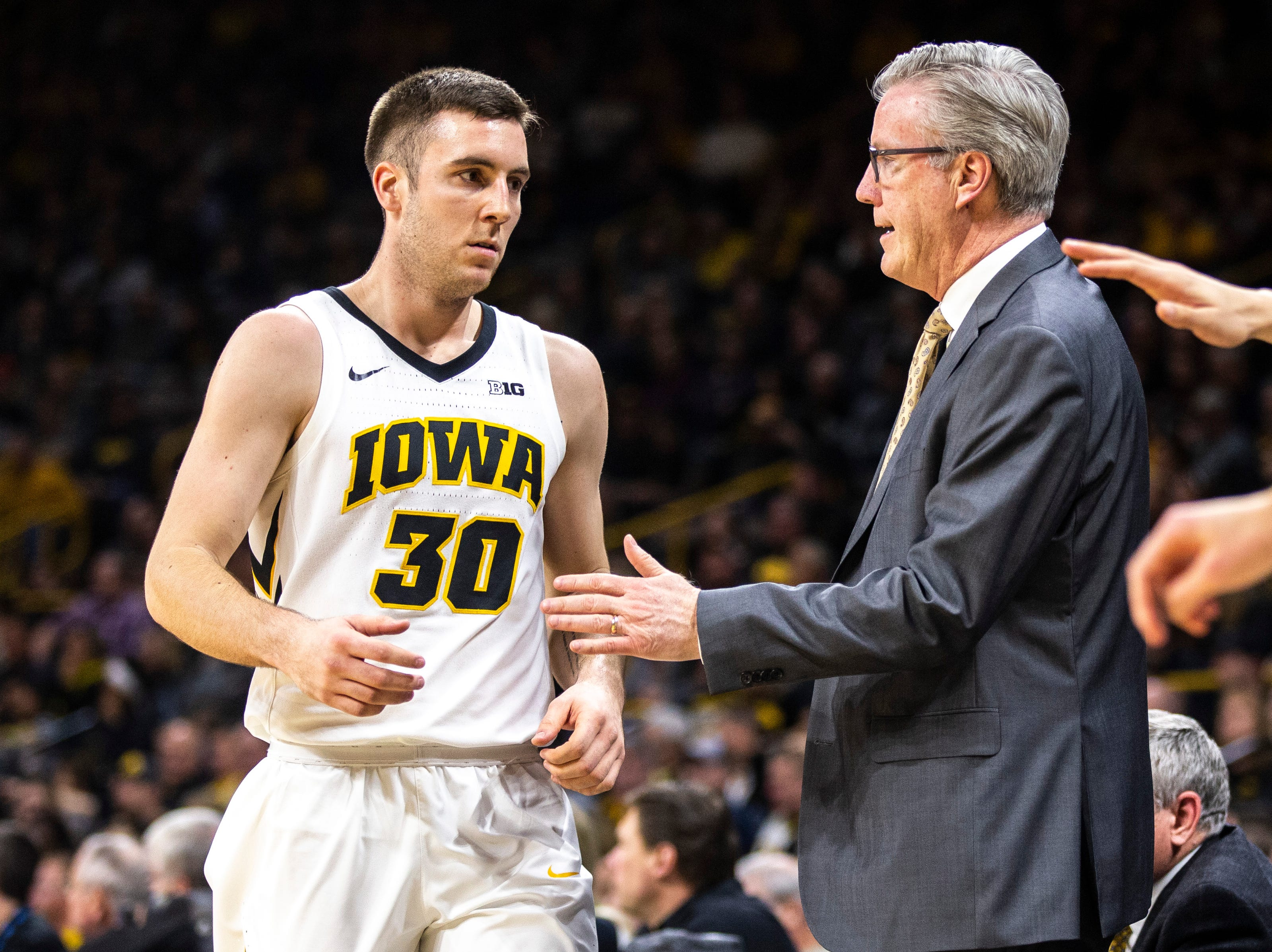 Iowa guard Connor McCaffery (30) heads to the bench past Iowa men's basketball head coach Fran McCaffery during a NCAA Big Ten Conference men's basketball game on Tuesday, Feb. 19, 2019 at Carver-Hawkeye Arena in Iowa City, Iowa.
