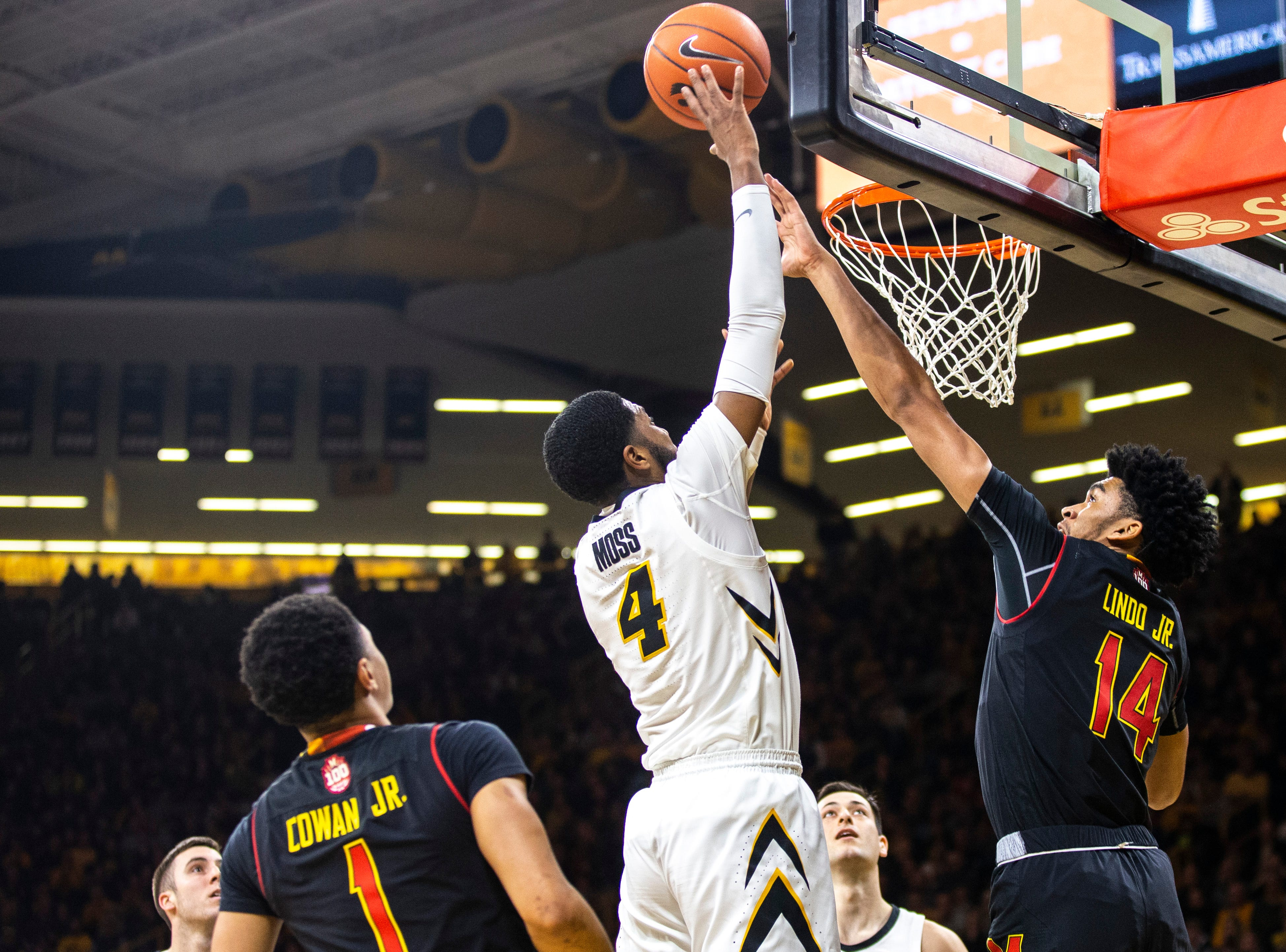 Iowa guard Isaiah Moss (4) makes a basket while Maryland forward Ricky Lindo Jr. (14) defends during a NCAA Big Ten Conference men's basketball game on Tuesday, Feb. 19, 2019 at Carver-Hawkeye Arena in Iowa City, Iowa.