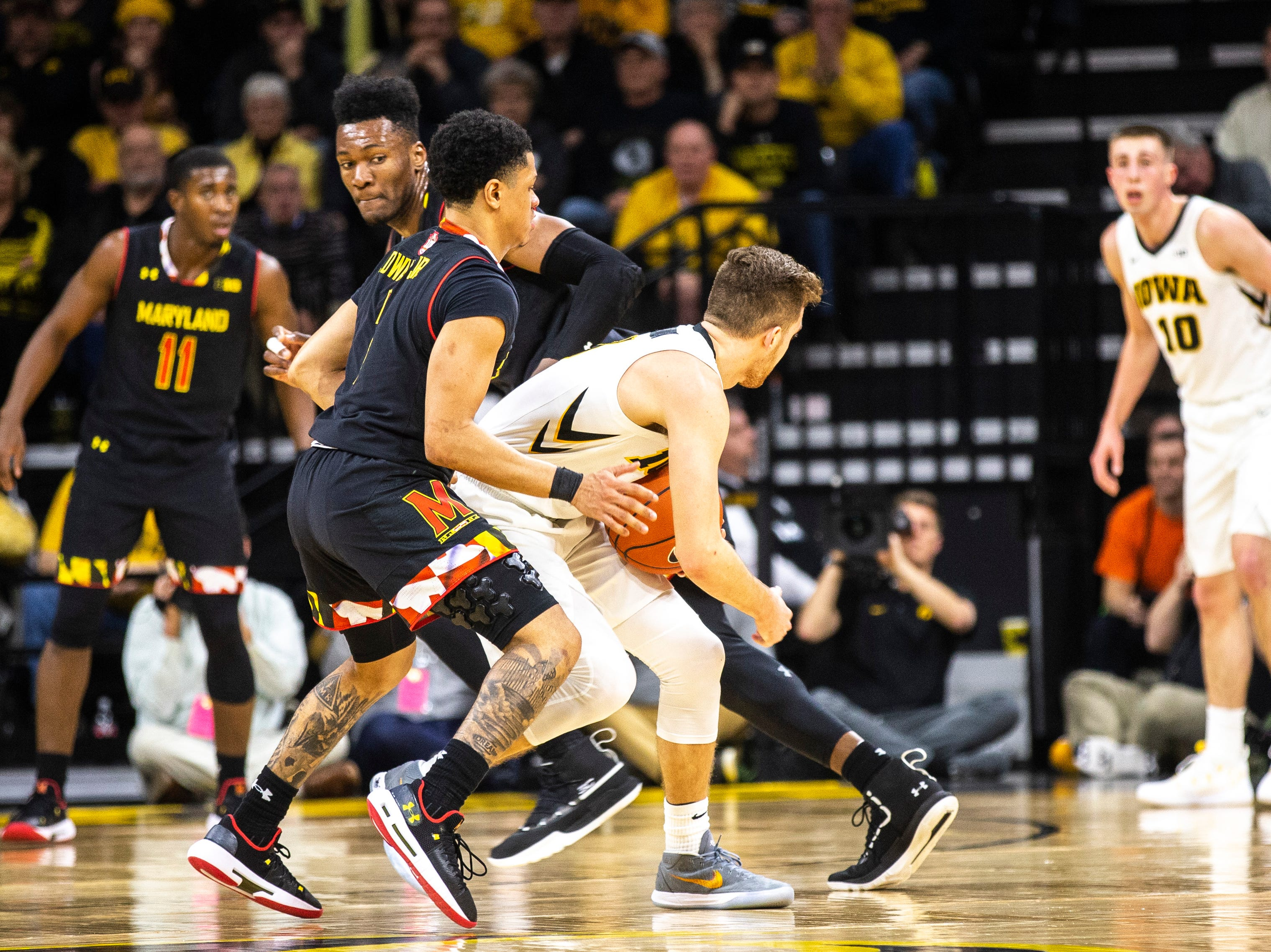 Iowa guard Jordan Bohannon (3) draws contact from Maryland guard Anthony Cowan Jr. (1) during a NCAA Big Ten Conference men's basketball game on Tuesday, Feb. 19, 2019 at Carver-Hawkeye Arena in Iowa City, Iowa.
