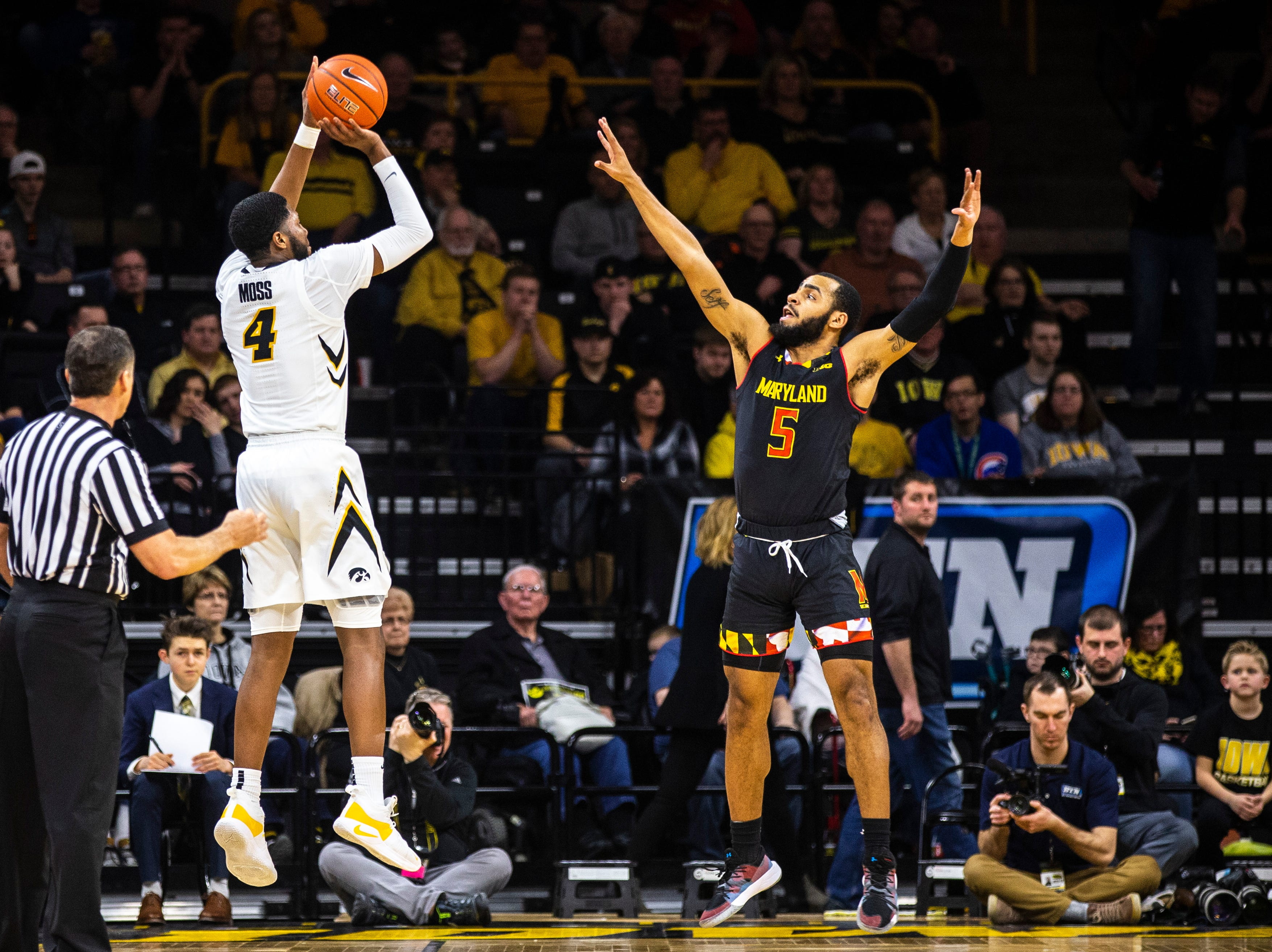 Iowa guard Isaiah Moss (4) rises to shoot a 3-point basket while Maryland guard Eric Ayala (5) defends during a NCAA Big Ten Conference men's basketball game on Tuesday, Feb. 19, 2019 at Carver-Hawkeye Arena in Iowa City, Iowa.