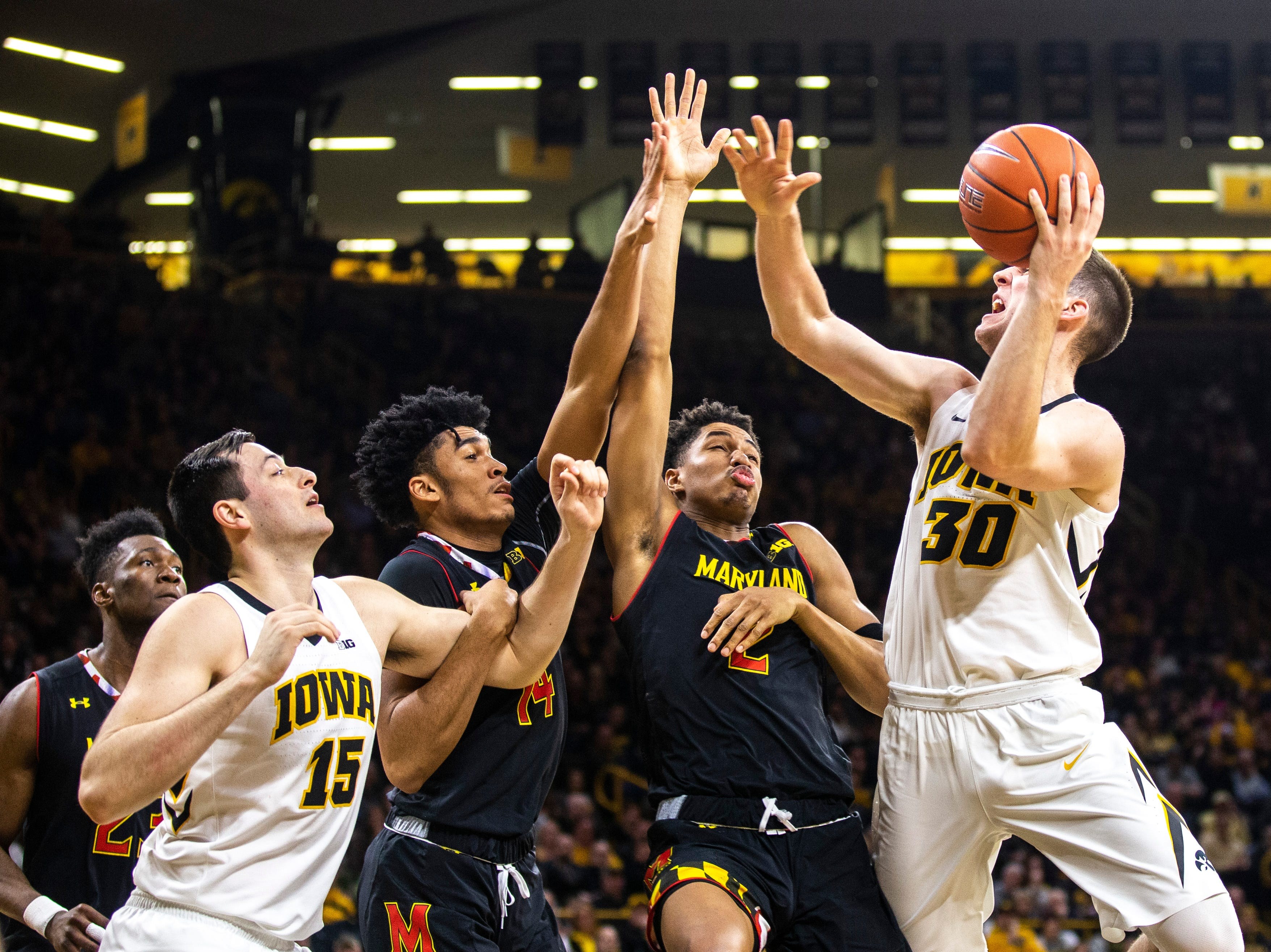 Iowa guard Connor McCaffery (30) drives to the basket while Maryland guard Aaron Wiggins (2) and Maryland forward Ricky Lindo Jr. (14) defend during a NCAA Big Ten Conference men's basketball game on Tuesday, Feb. 19, 2019 at Carver-Hawkeye Arena in Iowa City, Iowa.