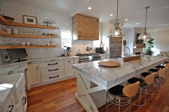 A large island with seating and a sink marks the kitchen at 7349 N. Pennsylvania St. in Meridian Hills, Friday, Feb. 15, 2019.  Marble countertops and wooden floors fill the room.