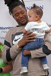 Shaquem Griffin holds Maylee Monbo during the event. He autographed her shirt.
