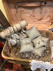 A vintage suitcase displays jewelry for sale atWhimsy Willows boutique at the Outlets of Mississippi.