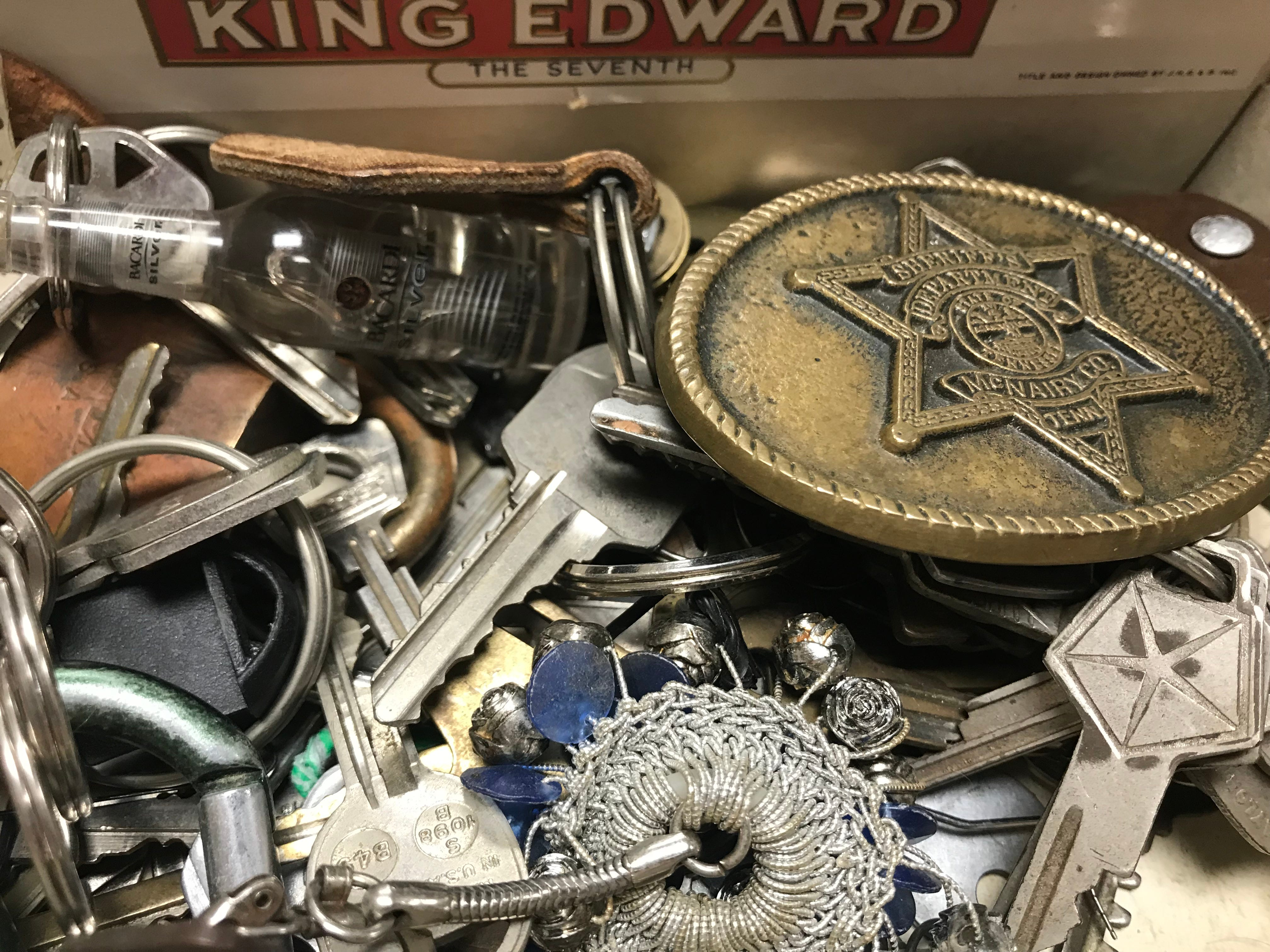 A McNairy County Sheriff's Department badge sits in a box of keys and trinkets  Madison County Sheriff's Office recovered from a theft ring believed to be targeting grieving families and others throughout West Tennessee.