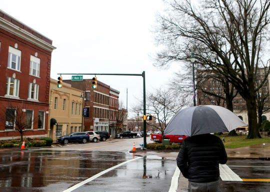 A man stands at the corner of Main Street and Liberty Street while waiting for a light to cross the street in downtown, Jackson, Tenn., on Wednesday, Feb. 20, 2019.