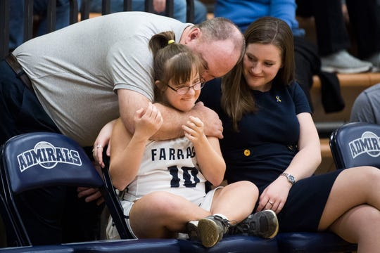 Joe Campbell hugs his daughter Olivia as her sister Natalie watches on at halftime of Olivia's senior night game at Farragut High School, Saturday, Feb. 2, 2019.