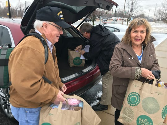 Rodney Vandeveer, Jim Hopf and Nina Barron-Burke, members of the Lafayette Kiwanis Club, carry sacks with homemade 50 comfort dolls into the Indiana State Police Post in Lafayette. The dolls are given to children involved in traumatic situations in hopes it will comfort their fears.