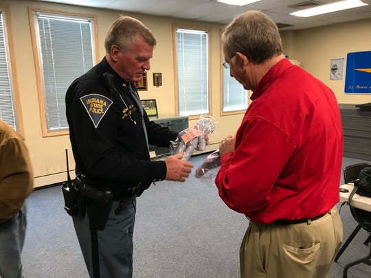 On behalf of the Indiana State Police, Sgt. Kim Riley accepts 50 homemade dolls donated Wednesday by the Lafayette Kiwanis and their past president, Jim Hopf.