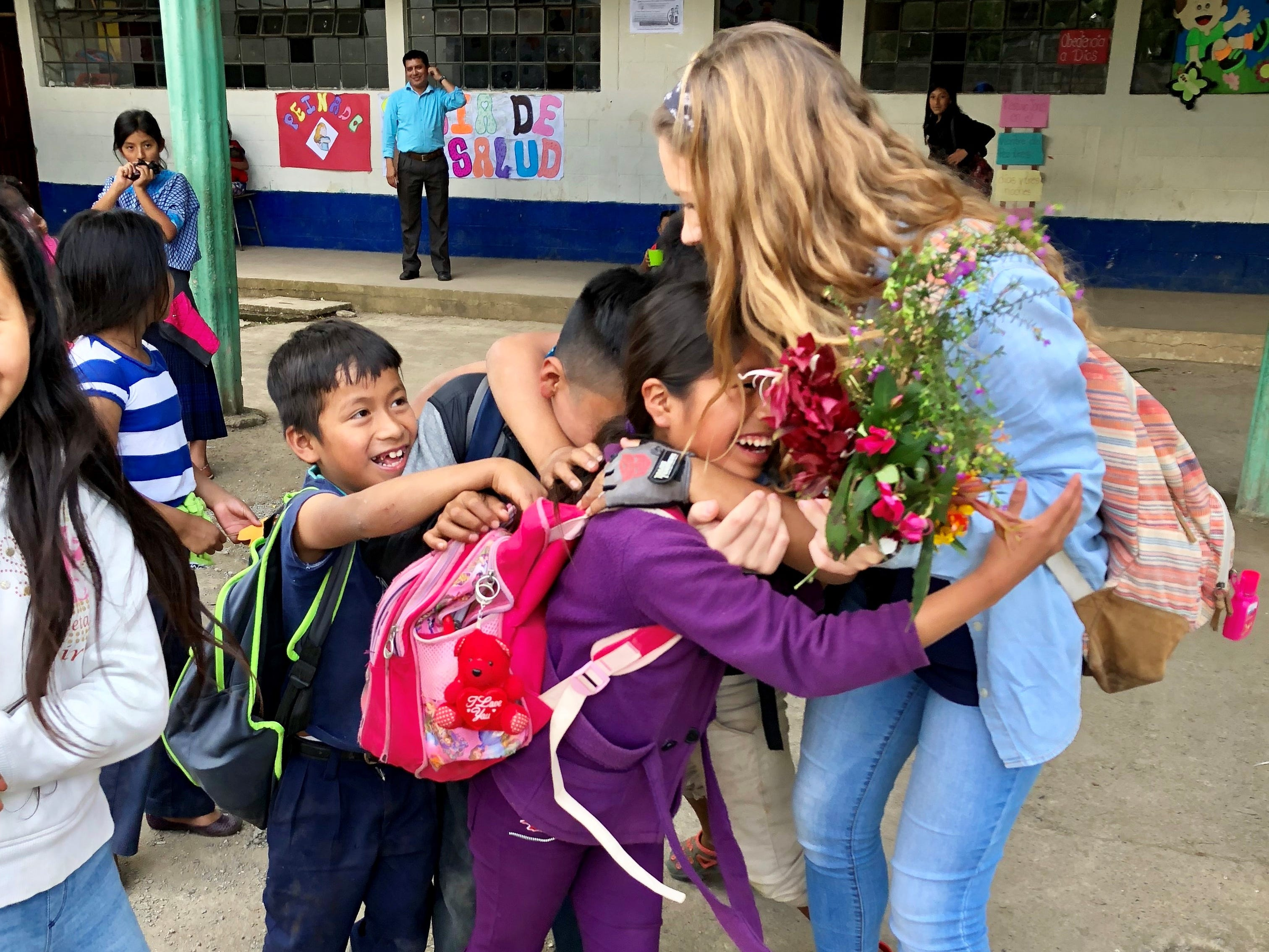 Cassidy Armstrong gets a group hug from elementary students at a school in Chicoyoj I, a rural community in Guatemala.