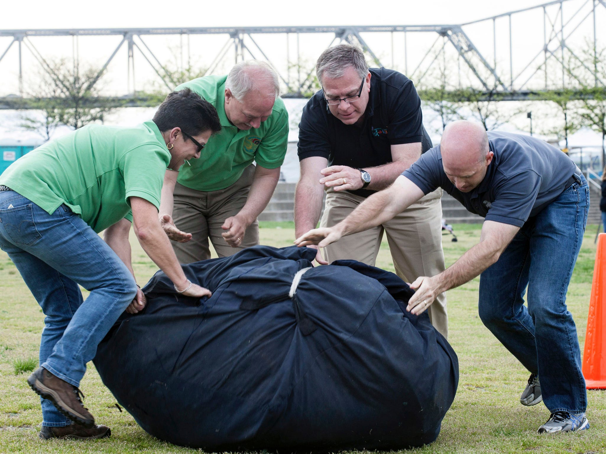 Left to right: Kentucky Derby Festival members Leslie Broecker, David Nett, Mike Berry and Jeff English complete the daunting task of pushing 225 pounds through a 75-foot obstacle course during the 2nd Annual Balloon Crew Challenge on the Waterfront Lawn Thursday night.  April 24, 2014